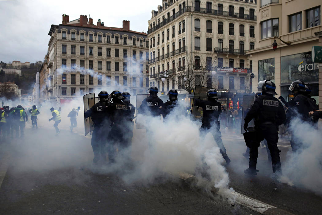 Police officers clash with demonstrators in Lyon, central France, Saturday, Dec. 8, 2018. The grassroots movement began as resistance against a rise in taxes for diesel and gasoline, but quickly e ...