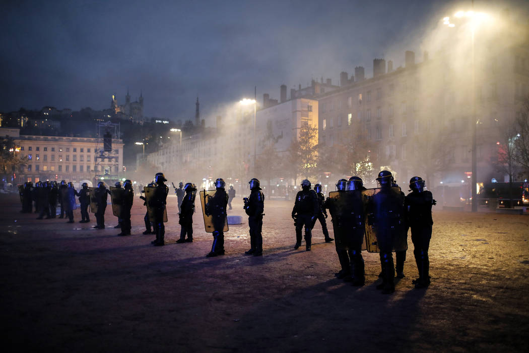 Police officers face demonstrators in Lyon, central France, Saturday, Dec. 8, 2018. The grassroots movement began as resistance against a rise in taxes for diesel and gasoline, but quickly expande ...