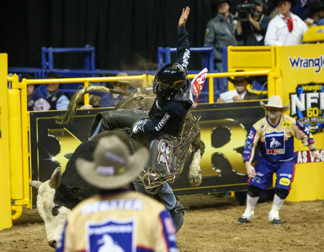 """Boudreaux Campbell, of Crockett, Texas, falls off of """"Lumberjack"""" while competing in bull riding during the fourth go-round of the National Finals Rodeo at the Thomas & Mack Center i ..."""
