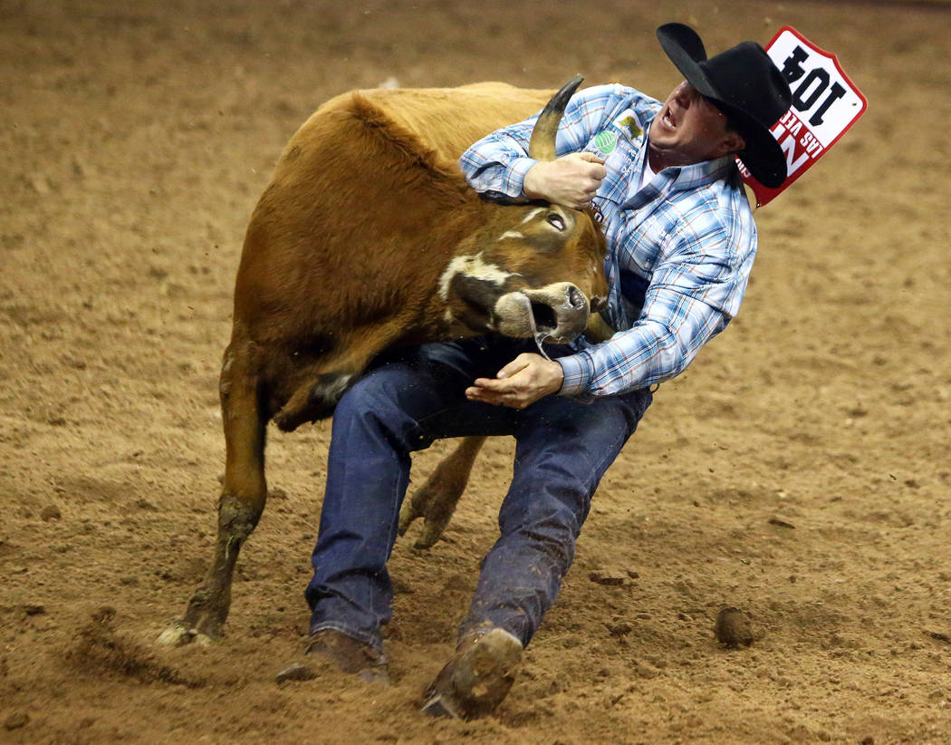 Nick Guy, of Sparta, Wis, competes in steer wrestling during the fourth go-round of the National Finals Rodeo at the Thomas & Mack Center in Las Vegas, Sunday, Dec. 9, 2018. Caroline Brehman/L ...