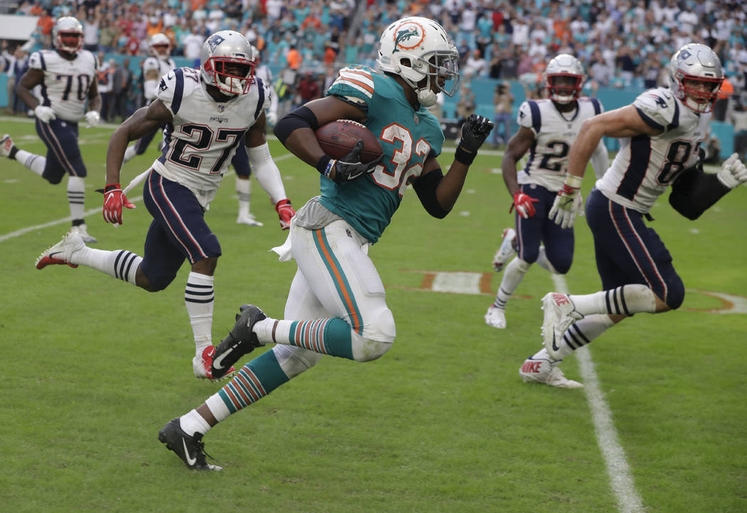 Miami Dolphins running back Kenyan Drake (32) runs for a touchdown during the second half of an NFL football game against the New England Patriots, Sunday, Dec. 9, 2018, in Miami Gardens, Fla. The ...