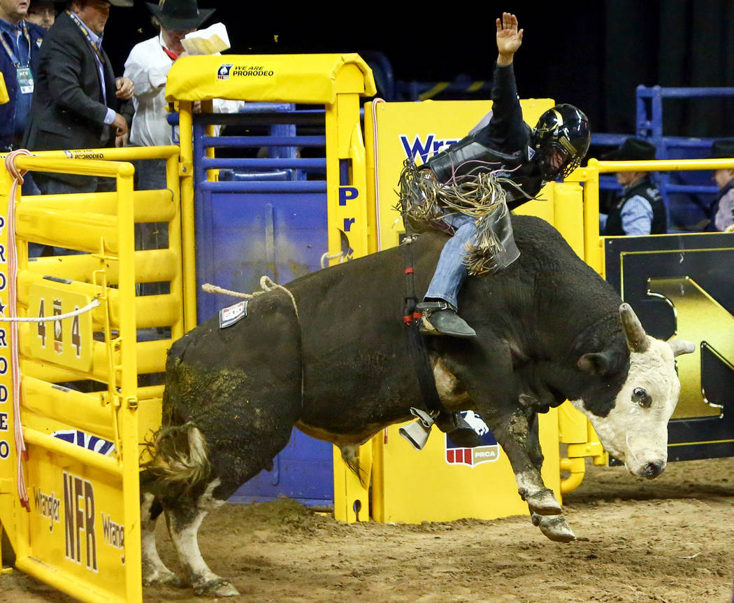 "Boudreaux Campbell, of Crockett, Texas, rides ""Lumberjack"" while competing in bull riding during the fourth go-round of the National Finals Rodeo at the Thomas & Mack Center in Las V ..."