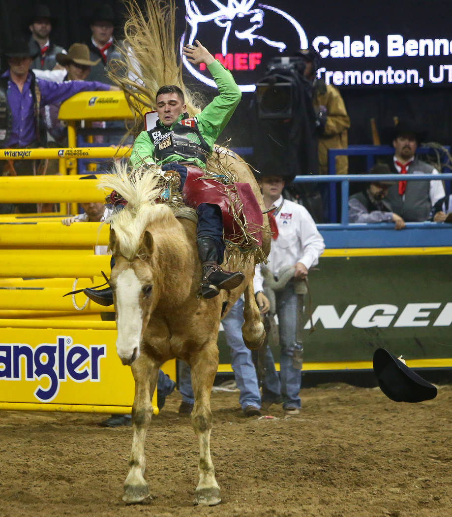 "Caleb Bennett, of Tremonton, Utah, rides ""Just Peachy"" while competing in Bareback Riding during the fourth go-round of the National Finals Rodeo at the Thomas & Mack Center in Las V ..."