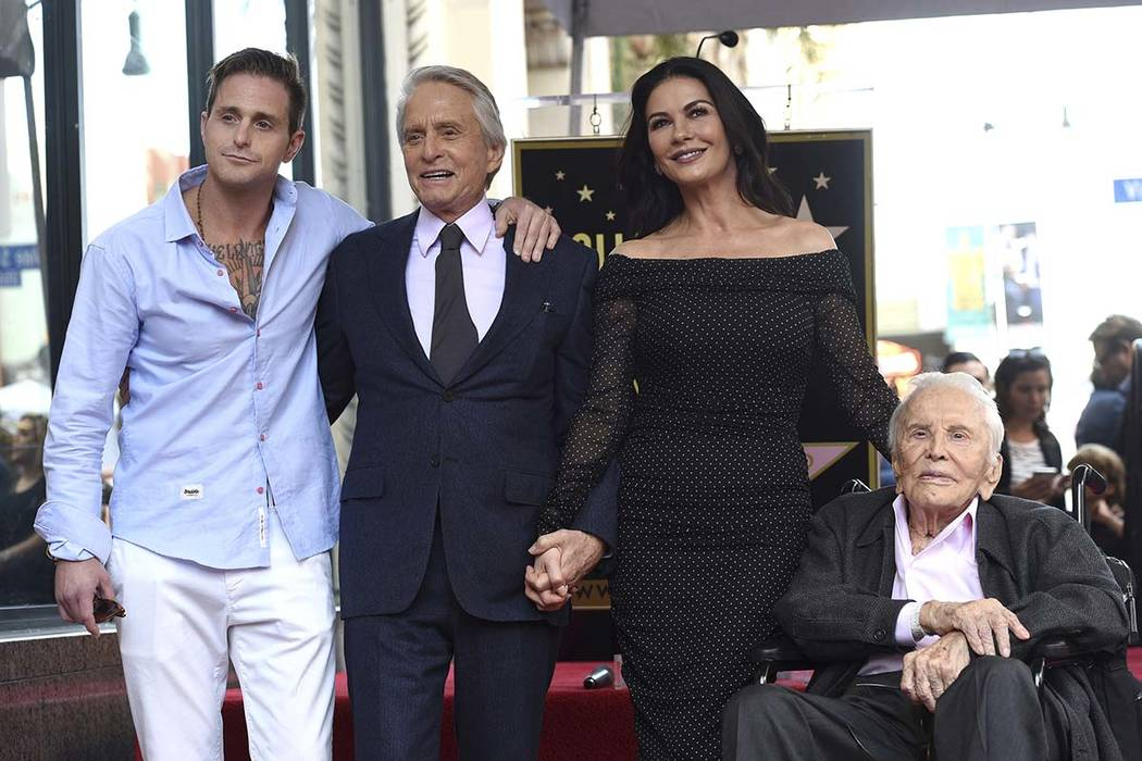 In this Nov. 6, 2018, file photo, Honoree and actor Michael Douglas, second left, poses with his father actor Kirk Douglas, from right, wife Catherine Zeta-Jones and son Cameron Douglas following ...