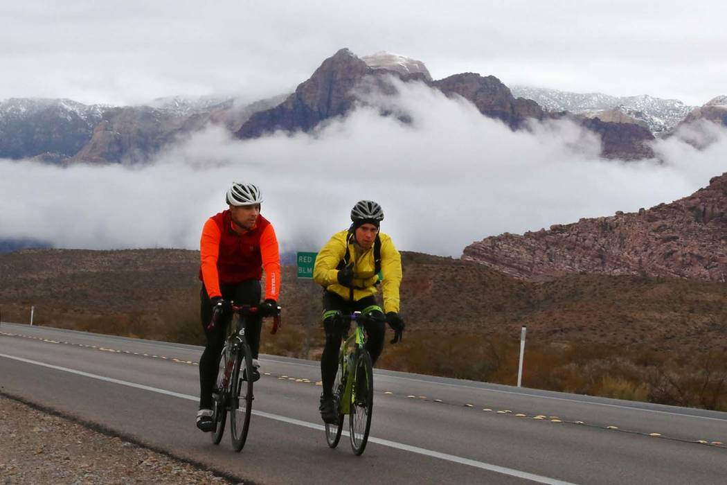 Bicyclists ride their bikes as clouds loom over Red Rock Canyon on Friday, Dec. 7, 2018, in Las Vegas. (Bizuayehu Tesfaye/Las Vegas Review-Journal) @bizutesfaye