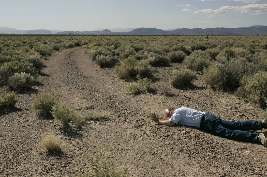 Melvin Dummar lies in the desert on Thursday, June 15, 2006 in the position and location where he claims to have found Howard Hughes in 1967. Dummar returned to the spot with a documentary film c ...