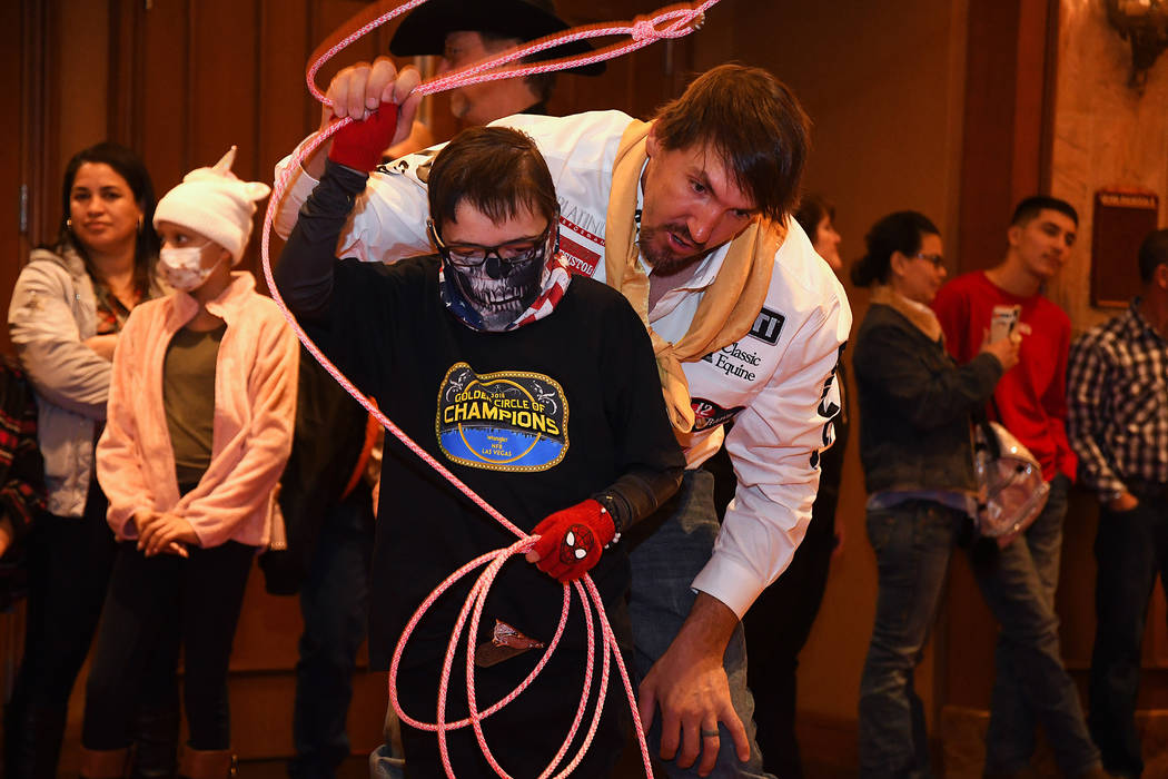 World champion steer wrestler Tyler Pearson gives a roping lesson to Gavin Kilcullen of Henderson, one of the children invited to the Golden Circle of Champions Banquet on Sunday at the South Poin ...