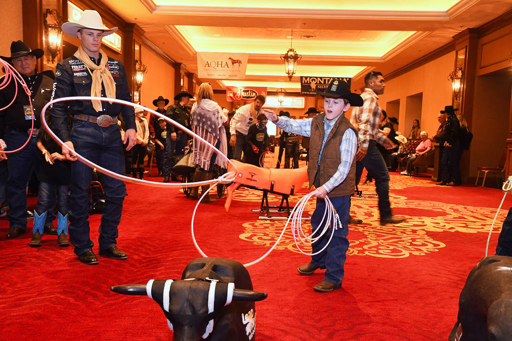 Wrangler NFR bull rider Joe Frost, right, checks out the roping form of Takota McAllister of Red Bluff, Calif., during Sunday's Golden Circle of Champions Banquet at the South Point. The event ben ...