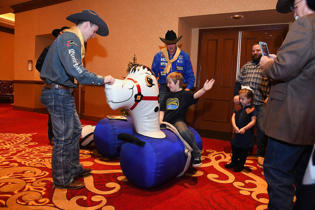Dorian Millett, middle, hangs on during a ride on an inflatable bouncy horse as Wrangler NFR contestants Tim O'Connell, left, and Kyle Irwin cheer him along during Sunday's Golden Circle of Champi ...