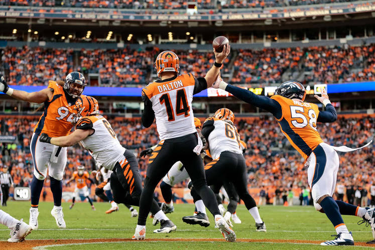 Nov 19, 2017; Denver, CO, USA; Cincinnati Bengals quarterback Andy Dalton (14) passes under pressure from Denver Broncos linebacker Von Miller (58) as quarterback Jeff Driskel (6) defends against ...