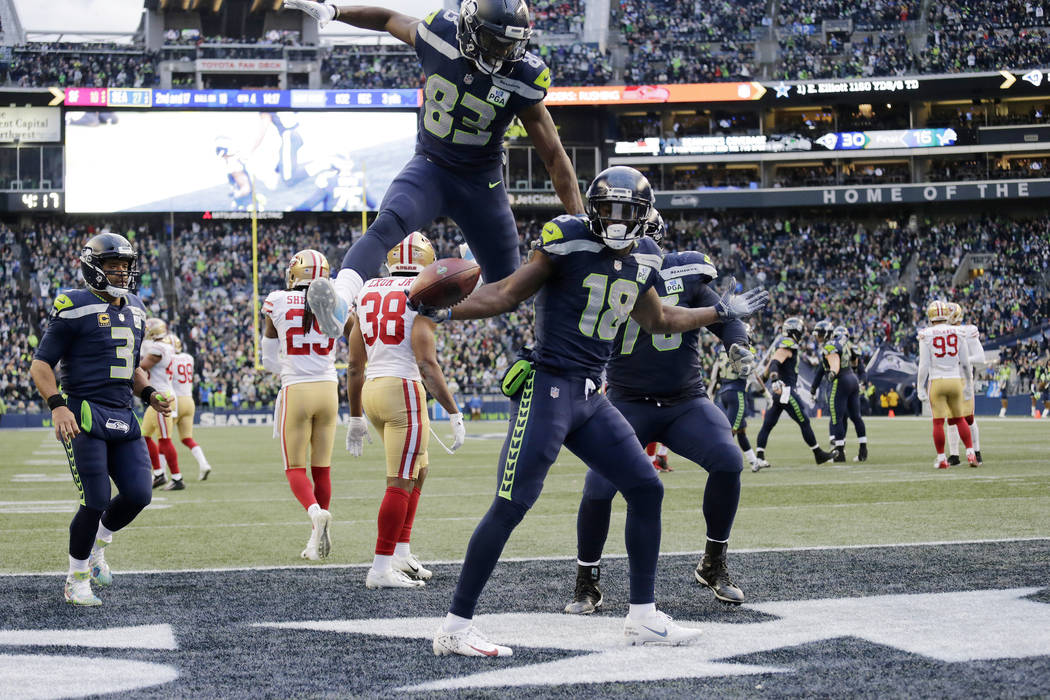 Seattle Seahawks wide receiver Jaron Brown, (18) celebrates with wide receiver David Moore (83) after Brown caught a pass for a touchdown during the second half of an NFL football game against the ...