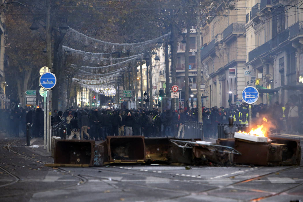 Demonstrators stand behind a burning bin during clashes, Saturday, Dec. 8, 2018 in Marseille, southern France. The rumble of armored police trucks and the hiss of tear gas filled central Paris on ...