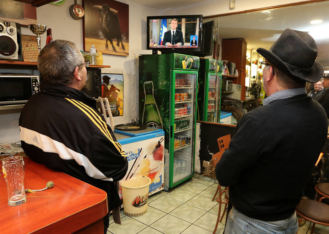 People watch French President Emmanuel Macron during a televised address to the nation, in Hendaye, southwestern France, Monday, Dec. 10, 2018. In an unusual admission, French President Emmanuel ...