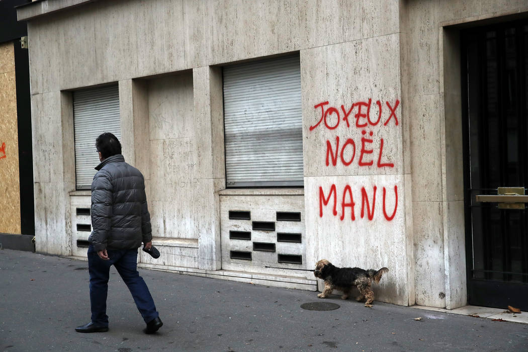A man walks his dog past a tag reading : Happy Christmas Manu, referring to French President Emmanuel Macron, in Paris, Sunday, Dec. 9, 2018. Paris monuments reopened, cleanup workers cleared debr ...