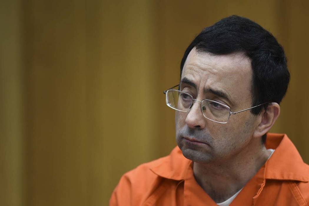 Larry Nassar listens as Rachael Denhollander gives her victim impact statement Friday, Feb. 2, 2018, the second and final day of victim impact statements in Judge Janet Cunningham's courtroom in C ...