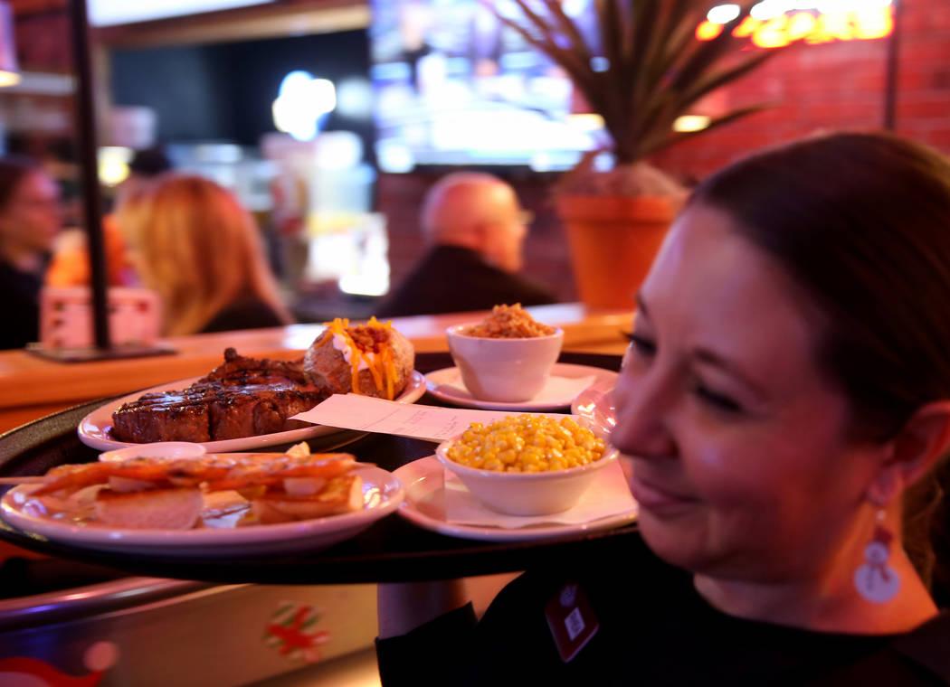 Server Rhea Lantelme delivers dinners at Texas Roadhouse at 1380 E. Craig Road in North Las Vegas Wednesday, Dec. 12, 2018. K.M. Cannon Las Vegas Review-Journal @KMCannonPhoto