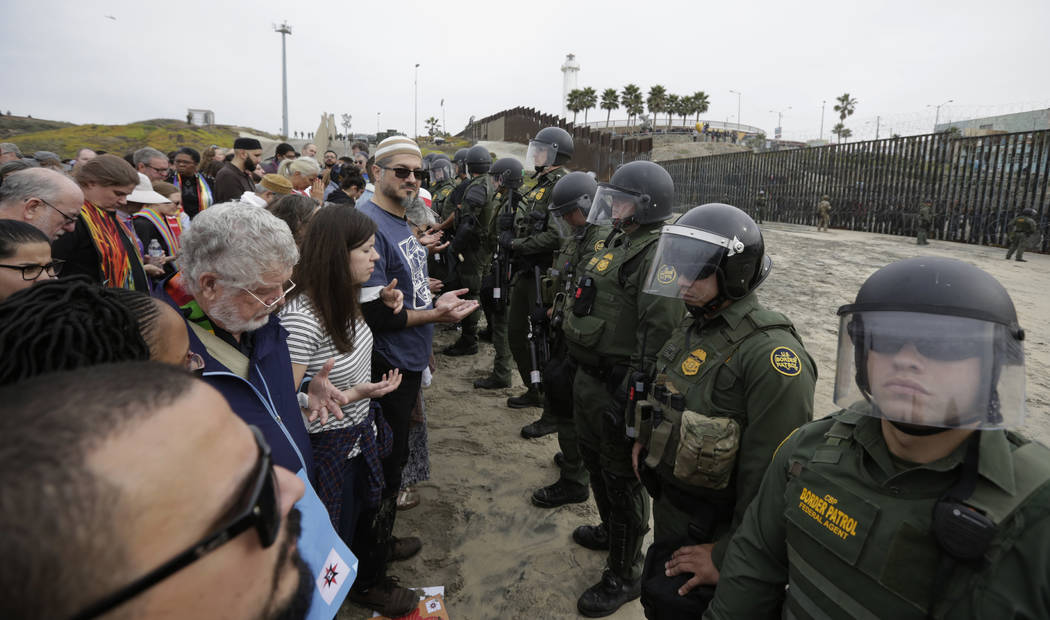 Immigrant rights activists stand arm in arm and line up against border patrol agents during a protest at the border wall in San Diego, Calif., Monday, Dec. 10, 2018. (AP Photo/Gregory Bull)
