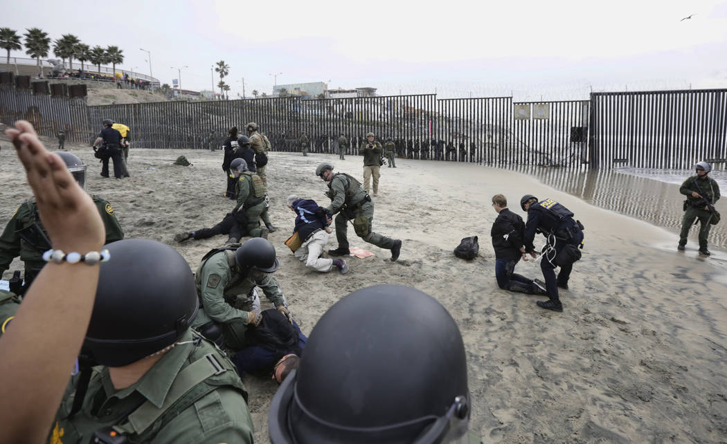 Immigrant rights activists are arrested by border patrol agents during a protest at the border wall in San Diego, Calif., Monday, Dec. 10, 2018. (AP Photo/Gregory Bull)