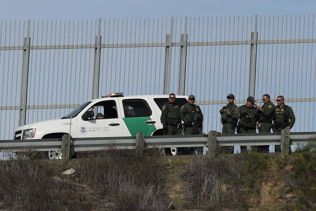U.S. Border Patrol agents stand in front of a secondary fence in San Diego, California looking across border wall toward Mexico as they respond to a group of Central American migrants who crossed ...
