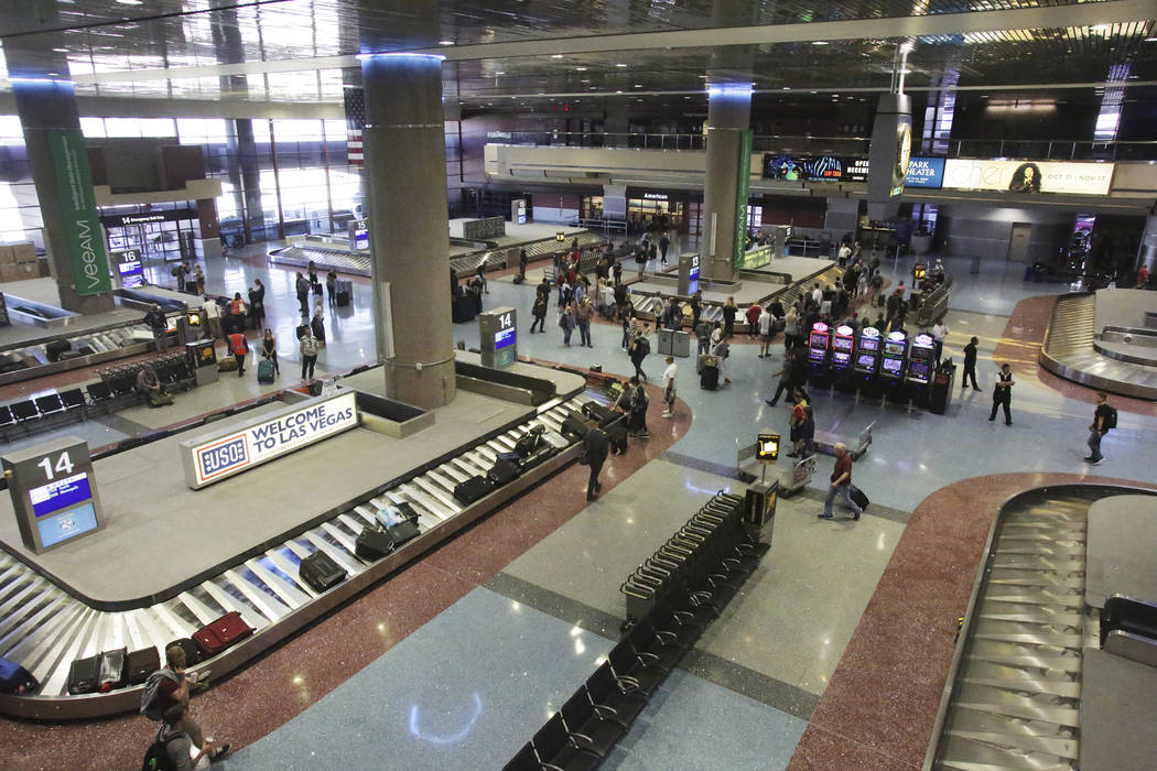 Travelers pick up their luggage on Friday, October, 19, 2018 at baggage claim in McCarran International Airport which just received a top ranking for quality from J.D. Power & Associates. Mich ...