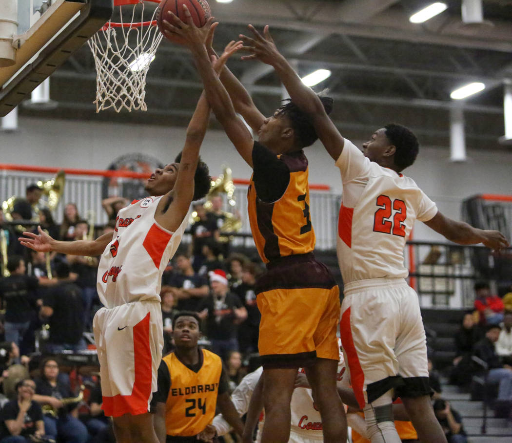 Eldorado's Jonathan Thomas (3) catches a rebound ball while under pressure from Chaparral's Miles Lewis-Disroe (5), left, and Jordan Harley (22) during the second half of a basketball game at Chap ...