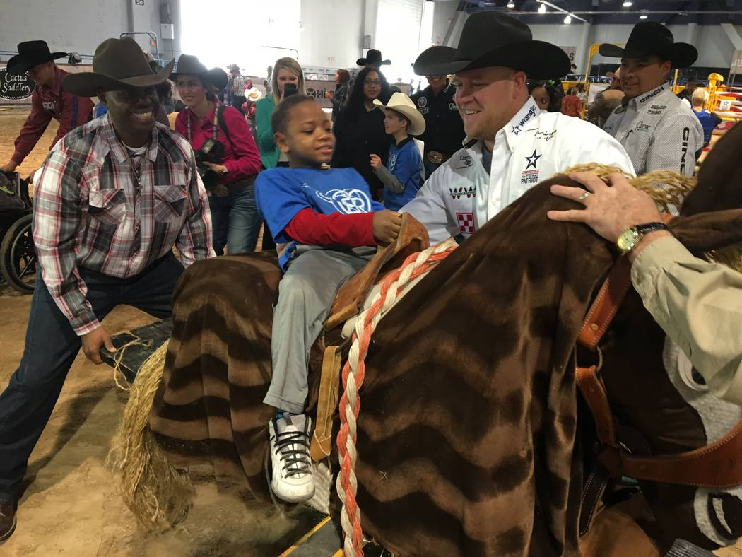Wrangler NFR steer wrestler Will Lummus, left, helps a youngster properly get into the saddle for a ride aboard Payback, a simulated bucking horse, during Monday's Exceptional Rodeo at the Wrangle ...