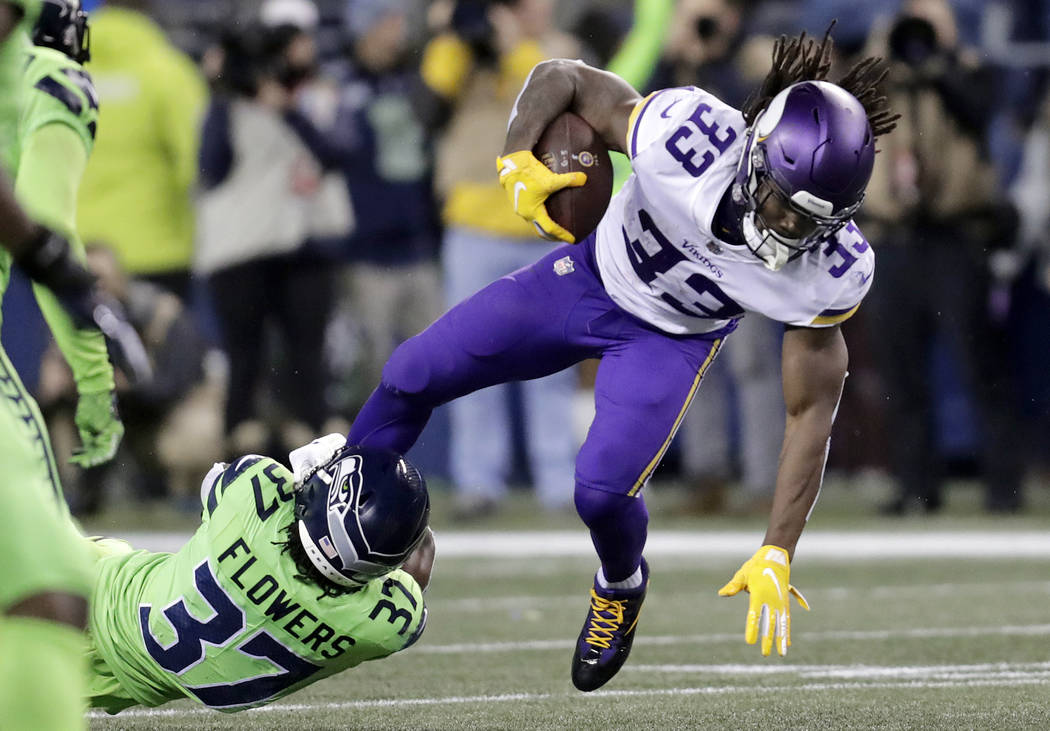 Minnesota Vikings' Dalvin Cook runs with the ball as Seattle Seahawks' Tre Flowers tries to bring him down in the first half of an NFL football game, Monday, Dec. 10, 2018, in Seattle. (AP Photo/S ...