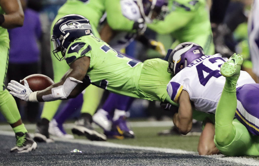 Seattle Seahawks' Chris Carson, left, dives into the end zone for a touchdown against the Minnesota Vikings in the second half of an NFL football game, Monday, Dec. 10, 2018, in Seattle. (AP Photo ...