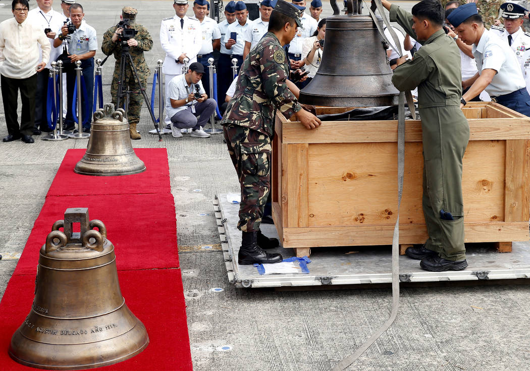 Philippine Air Force personnel unload three church bells seized by American troops as war trophies more than a century ago, as they are flown back Tuesday, Dec. 11, 2018 in suburban Pasay city, so ...