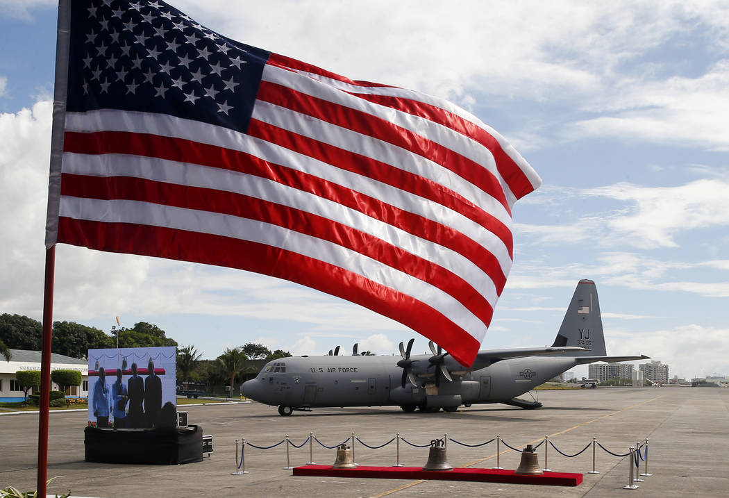 An American flag flutters as three church bells seized by American troops as war trophies more than a century ago, arrive Tuesday, Dec. 11, 2018 in suburban Pasay city、 southeast of Manila, ...