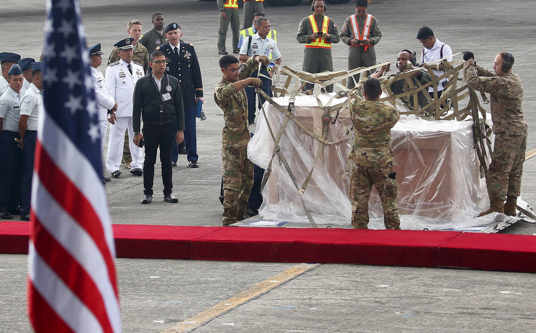 U.S. Air Force personnel prepare to unload three church bells seized by American troops as war trophies more than a century ago, as they were returned to the Philippines Tuesday, Dec. 11, 2018 in ...