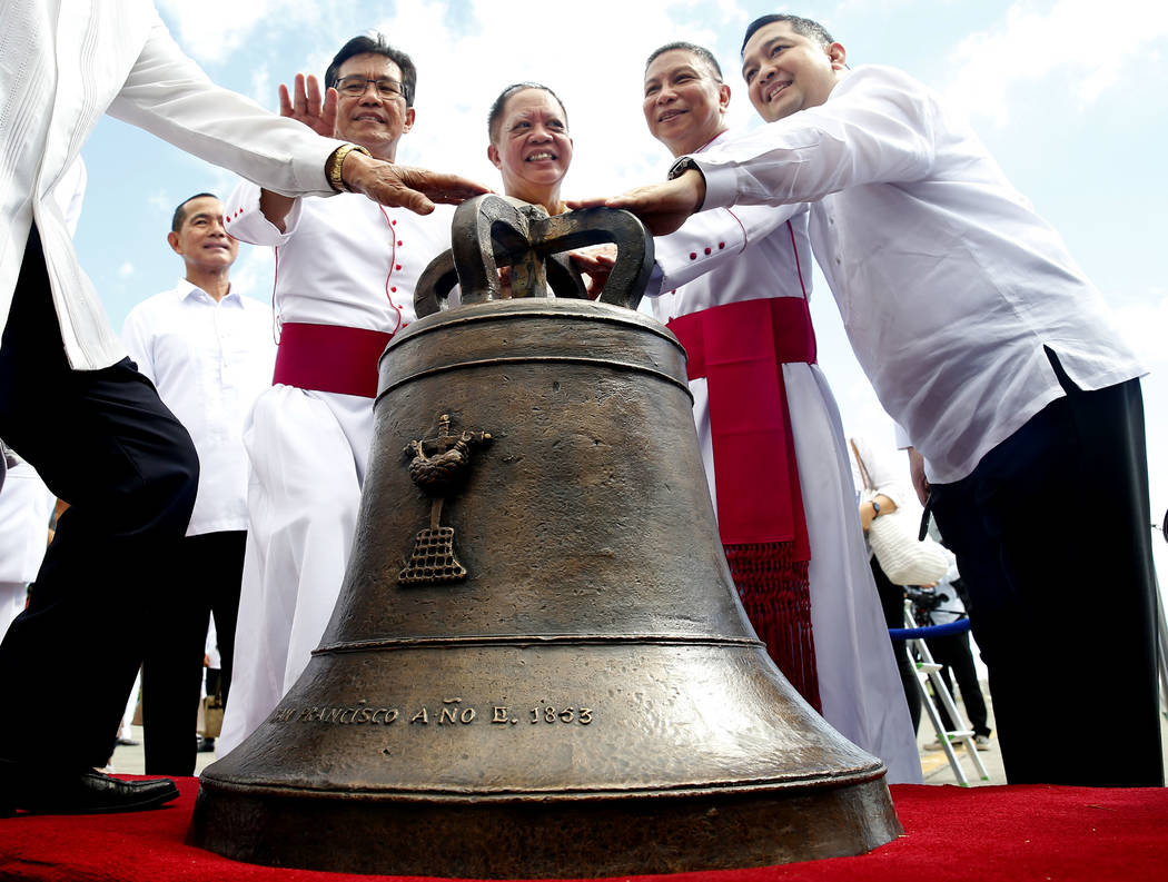 Roman Catholic priest Monsignor Pepe Quitorio, second from left, poses with other priests and officials before one of three church bells seized by American troops as war trophies more than a centu ...