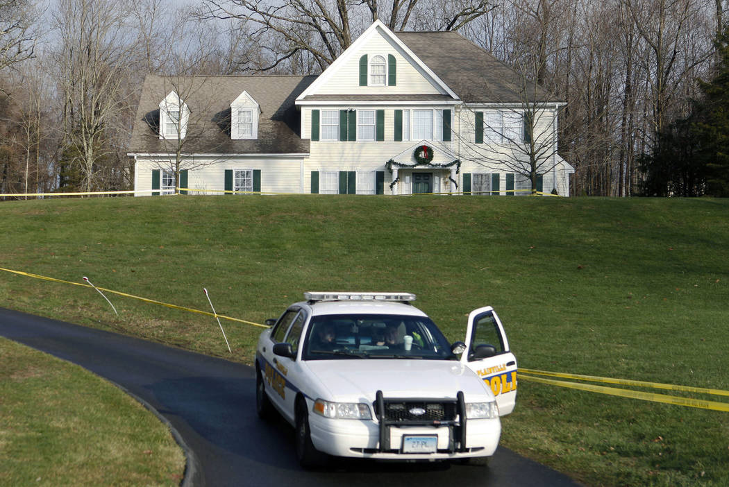 A police cruiser sits in the driveway of the home of Nancy Lanza in Newtown, Conn., Dec. 18, 2012, the Colonial-style house where she had lived with her son Adam Lanza. Documents from the investig ...