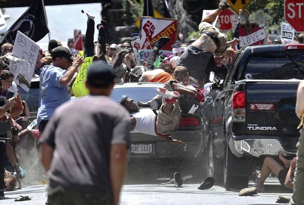 People fly into the air as a vehicle is driven into a group of protesters demonstrating against a white nationalist rally in Charlottesville, Va., Aug. 12, 2017. James Alex Fields Jr., accused of ...