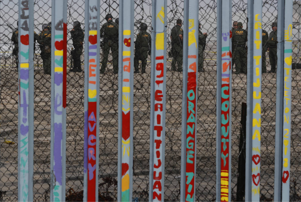 U.S. Border Patrol agents stand guard on the other side of the border in San Diego as they prepare for the arrival of hundreds of pro-migration protestors, seen through the border fence from Tijua ...
