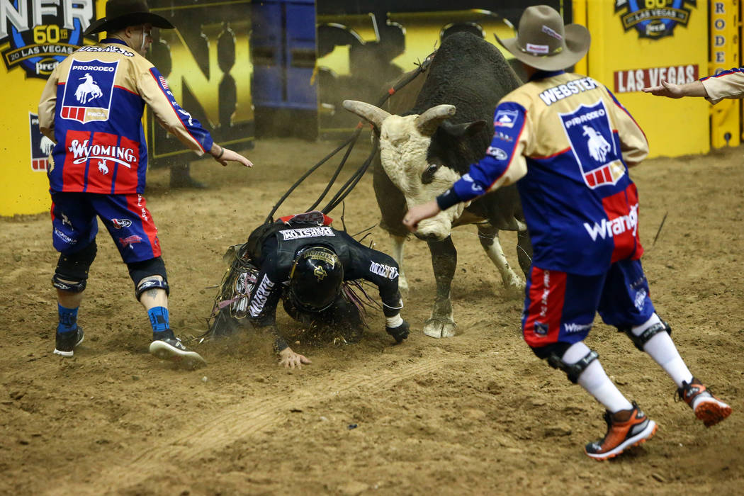 "Boudreaux Campbell, of Crockett, Texas, falls off of ""Lumberjack"" while competing in bull riding during the fourth go-round of the National Finals Rodeo at the Thomas & Mack Center i ..."
