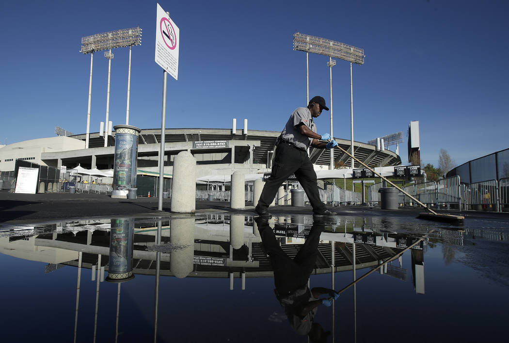 A worker cleans a puddle outside of Oakland Alameda County Coliseum before an NFL football game between the Oakland Raiders and the Kansas City Chiefs in Oakland, Calif., Sunday, Dec. 2, 2018. (AP ...