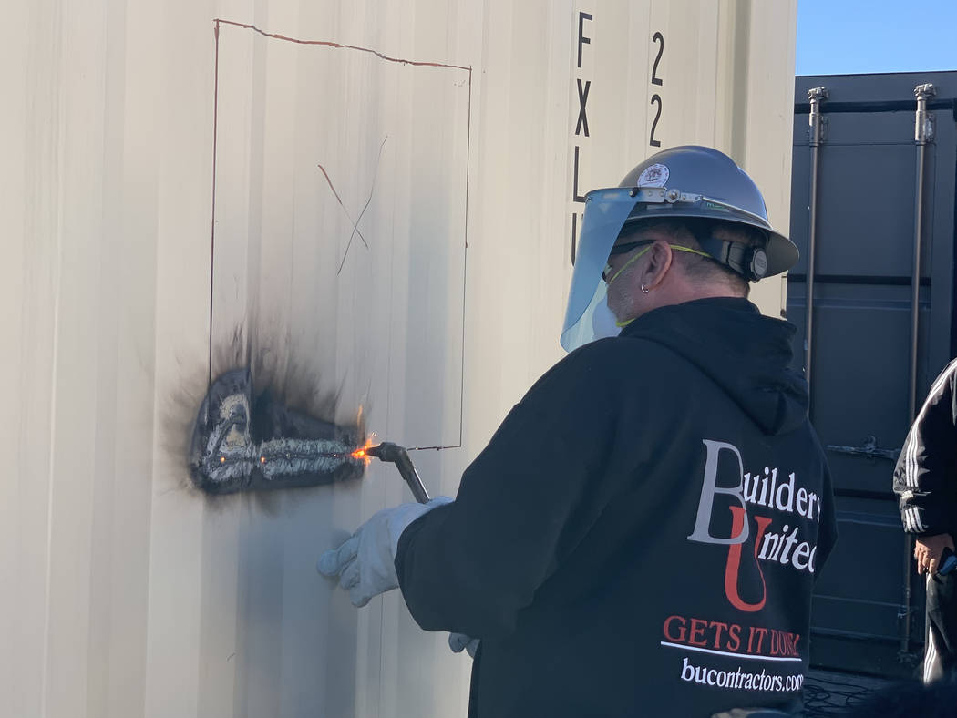 Symbolizing a ribbon cutting, Rick Rainy of Builders United uses a welding torch to start the first cut on a new container home at Veterans Village II, 50 N. 21st Street in Las Vegas on Tuesday, D ...