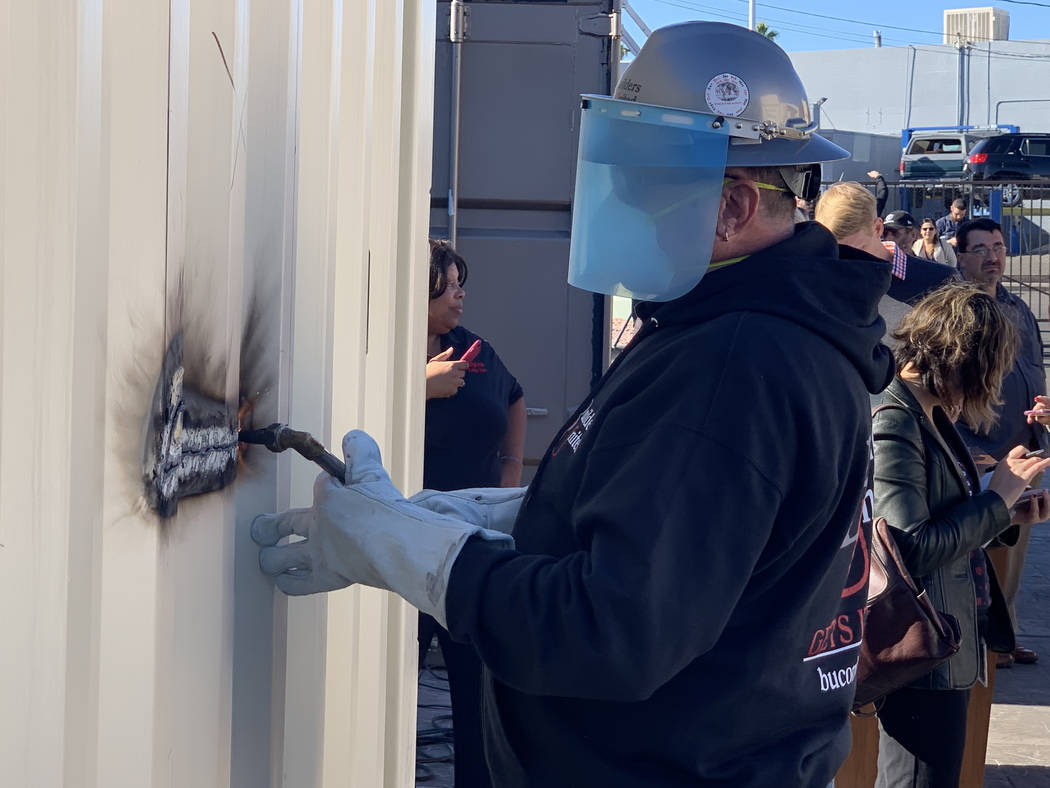 Symbolizing a ribbon cutting, Rick Rainy of Builders United uses a welding torch to start the first cut on a new container home at Veterans Village II, 50 N. 21st Street in Las Vegas, on Tuesday, ...