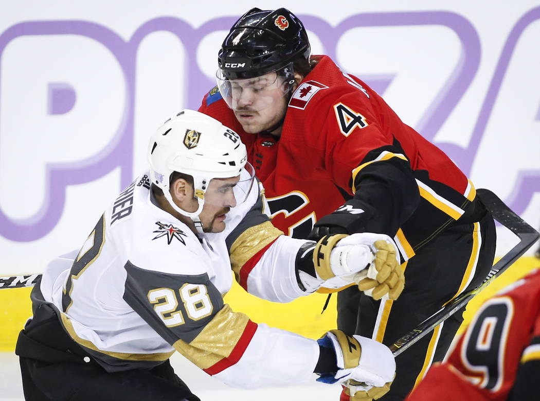 Vegas Golden Knights' William Carrier, left, checks Calgary Flames' Rasmus Andersson, of Sweden, during first-period NHL hockey game action in Calgary, Alberta, Monday, Nov. 19, 2018. (Jeff McInto ...