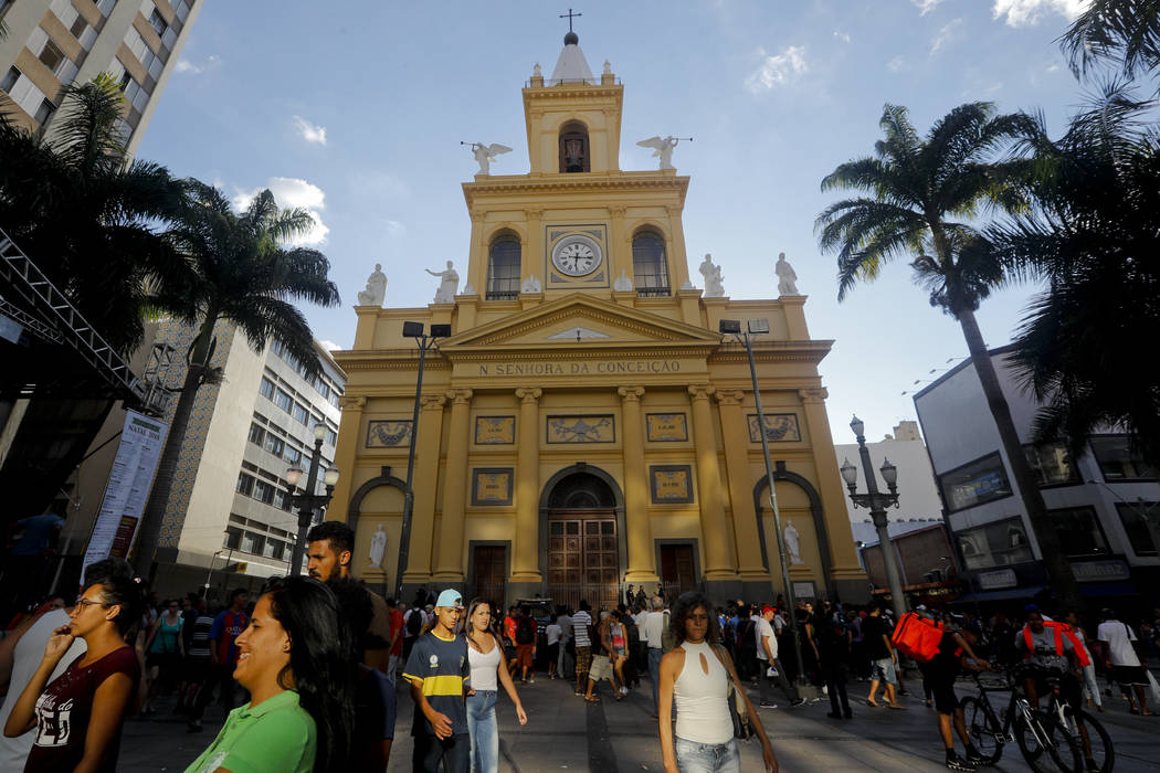People walk outside the Metropolitan Cathedral after a fatal shooting in Campinas, Brazil, Tuesday, Dec. 11, 2018. A man opened fire in the cathedral in southern Brazil after Mass on Tuesday, kill ...