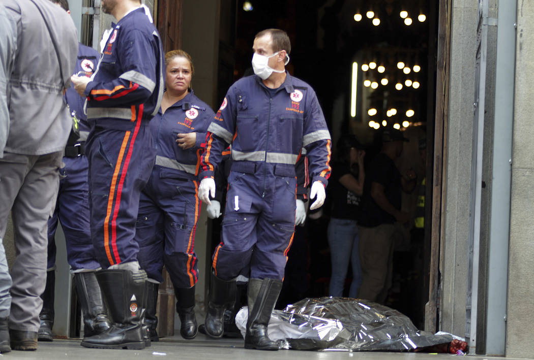 A firefighter walks next to a victim killed at the Metropolitan Cathedral in Campinas, Brazil, Tuesday, Dec.11, 2018. Authorities say an armed man entered the cathedral in southern Brazil on Tuesd ...