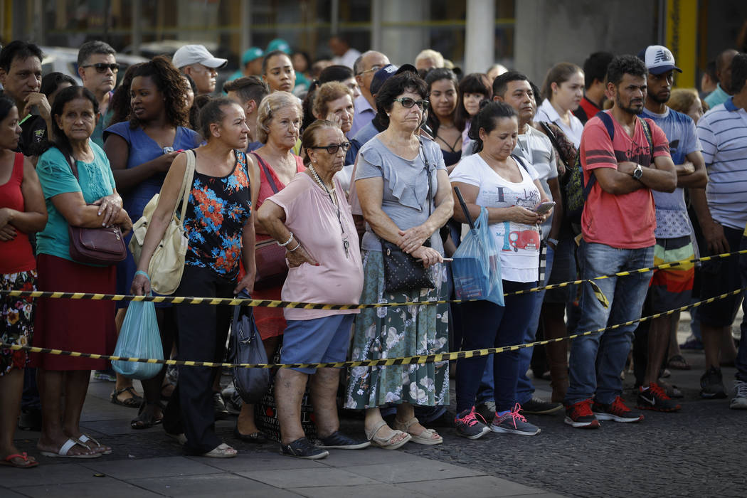 People stand outside the Metropolitan Cathedral in Campinas, Brazil, Tuesday, Dec. 11, 2018. A man opened fire in the cathedral, killing four and leaving four others injured, before taking a bulle ...