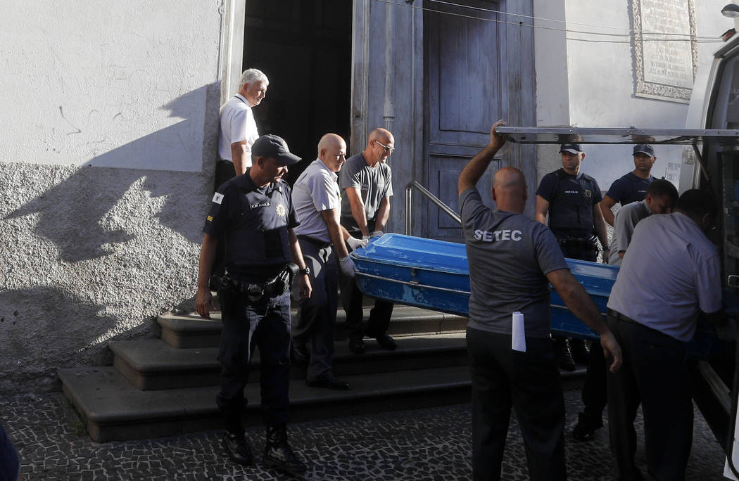 Police remove the body of a shooting victim from the Metropolitan Cathedral in Campinas, Brazil, Tuesday, Dec. 11, 2018. A man opened fire in the cathedral after Mass on Tuesday, killing four and ...