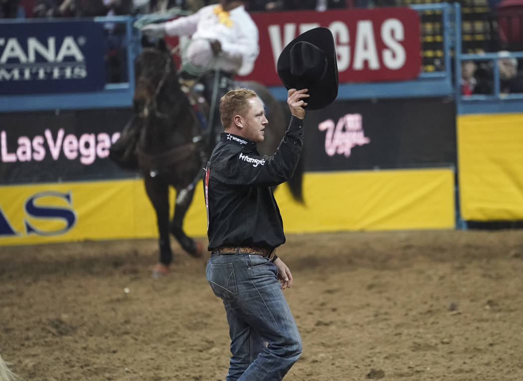 Curtis Cassidy of Alberta, Canada waives to the crowd after competing in the steer wrestling event during the sixth go-round of the National Finals Rodeo at the Thomas & Mack Center in Las Veg ...