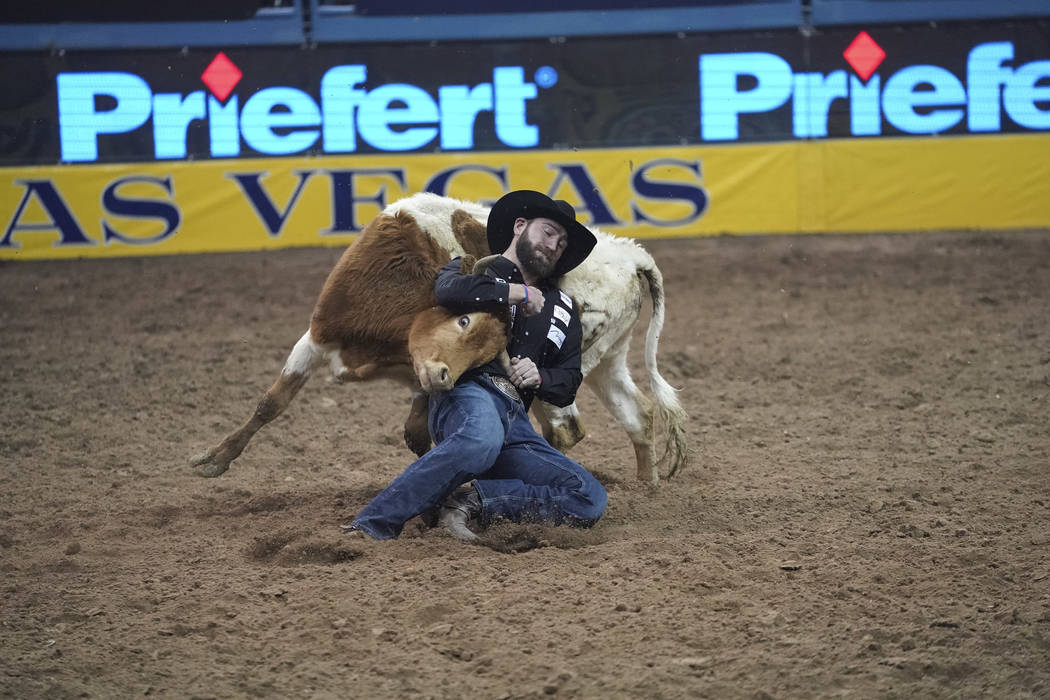 Bridger Chambers of Stevensville, Mont. competes in the steer wrestling event during the sixth go-round of the National Finals Rodeo at the Thomas & Mack Center in Las Vegas on Tuesday, Dec. 1 ...