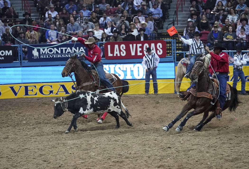 Trey Yates of Pueblo, Colo., left, and Aaron Tsinigine of Tuba City, Ariz. compete in the team roping event during the sixth go-round of the National Finals Rodeo at the Thomas & Mack Center i ...