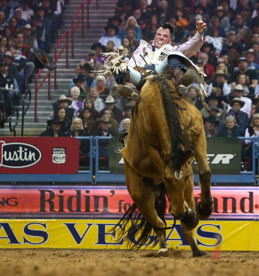 "Richmond Champion of The Woodlands, Texas (24) rides ""Imperial Beach"" while competing in Bareback Riding during the sixth go-round of the National Finals Rodeo at the Thomas & Mack C ..."