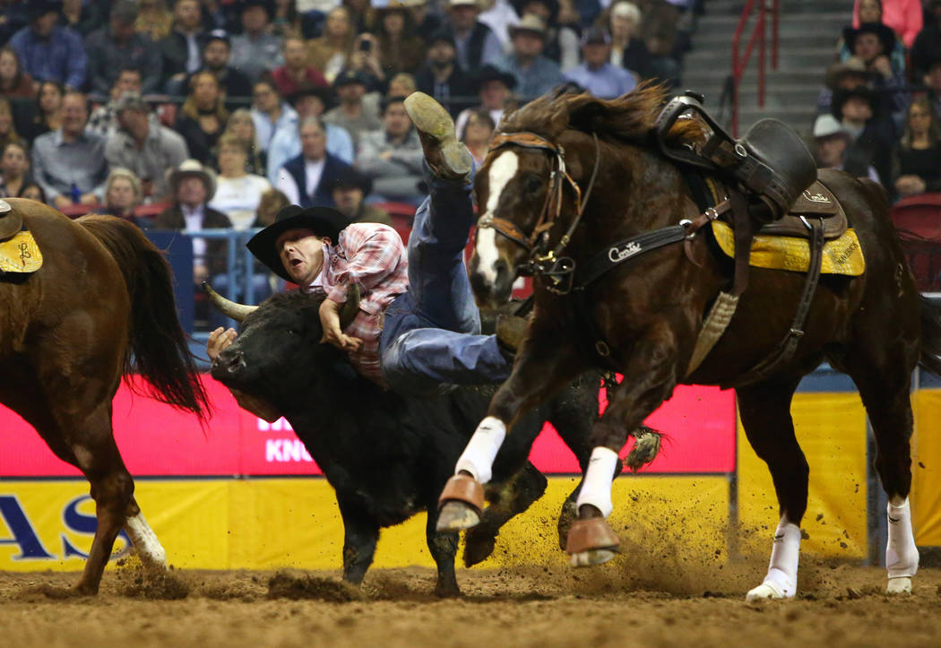 Nick Guy of Sparta, Wis. (104) jumps onto a steer while competing in steer wrestling during the sixth go-round of the National Finals Rodeo at the Thomas & Mack Center in Las Vegas, Tuesday, D ...