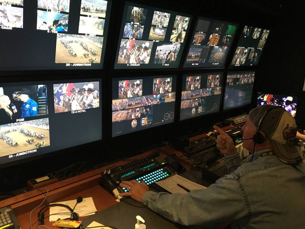 Rick Davidson, director of the Wrangler NFR's live satellite feed, fires instructions to his camera crew inside the Thomas & Mack Center, from his post in the production trailer outside the arena, ...